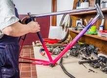 Las manos del bastidor real de la limpieza del mecánico de la bicicleta bike Foto de archivo