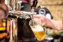 las manos del camarero en la cerveza golpean ligeramente la colada de una porción de la cerveza de cerveza dorada del proyecto en Fotos de archivo