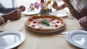Las manos del camarero fijan en la tabla una pizza a los amigos jovenes en restaurante metrajes