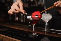 Las manos del camarero que adornan un cóctel rojo beben con una rebanada de una remolacha Imagen de archivo libre de regalías