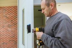 Las manos del carpintero de la puerta interior de la instalación instalan la cerradura foto de archivo