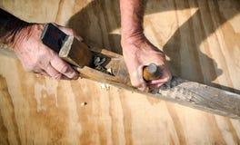 Las manos del carpintero que trabajan con la ensambladora de madera vieja Imágenes de archivo libres de regalías