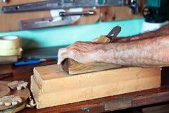 Las manos del carpintero que trabajan con madera Fotografía de archivo libre de regalías