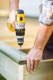 Las manos del carpintero usando el taladro en la madera Foto de archivo