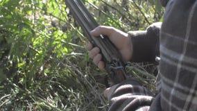 Las manos del cazador cargan un arma de dos cañones metrajes