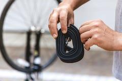 Las manos del ciclista están sosteniendo la cámara de goma derrumbada de la bicicleta imagen de archivo