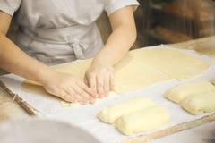 Las manos del cocinero amasan suavemente la pasta Poco panader?a de la familia foto de archivo libre de regalías