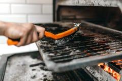Las manos del cocinero con el metal cepillan limpio el horno de la parrilla imagen de archivo