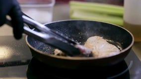 Las manos del cocinero de sexo masculino cocinan freír la carne en cocina almacen de video