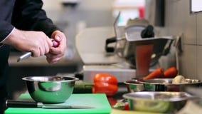 Las manos del cocinero de sexo masculino cocinan la cebolla de la peladura en cocina almacen de video