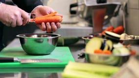 Las manos del cocinero de sexo masculino cocinan la zanahoria de la peladura en cocina almacen de metraje de vídeo