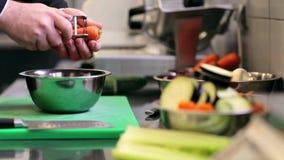 Las manos del cocinero de sexo masculino cocinan la zanahoria de la peladura en cocina almacen de video