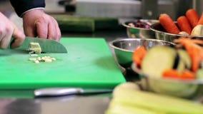 Las manos del cocinero de sexo masculino cocinan tajar el ajo en cocina metrajes