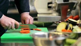 Las manos del cocinero de sexo masculino cocinan tajar la zanahoria en cocina almacen de metraje de vídeo