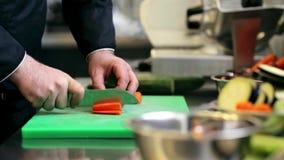 Las manos del cocinero de sexo masculino cocinan tajar la zanahoria en cocina almacen de video