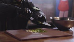 Las manos del cocinero en guantes negros del cocinero cortaron la cebolla verde en cierre del tablero de madera El hombre pone la almacen de metraje de vídeo
