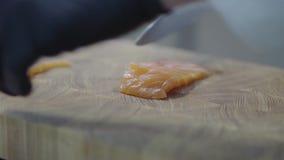 Las manos del cocinero en los guantes de goma negros que cortan salmones en el tablero de madera en primer moderno del restaurant almacen de video