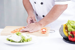 Las manos del cocinero que cortan el tomate Fotografía de archivo