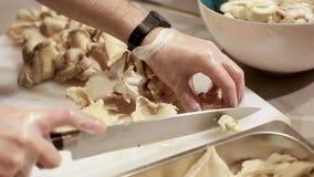 Las manos del cocinero que preparan setas en tabla de cortar en cocina metrajes
