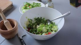 Las manos del cocinero vierten el aceite de oliva y el vinagre balsámico, ensalada verde almacen de video
