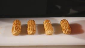 Las manos del confitero hacen hábilmente una obra maestra culinaria en tienda de chucherías o tienda de pasteles Producción, indu imagenes de archivo