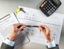 Las manos del constructor con llave y la vivienda elaboran el pensamiento en la negociación fotos de archivo libres de regalías