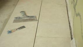 Las manos del constructor toman las tejas con una espátula y una paleta almacen de video