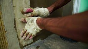 Las manos del constructor Yeso del mortero de la pared del oshtukaturivayut del empleado almacen de video