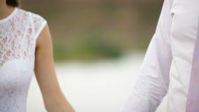 Las manos del control de novia y del novio en una boda caminan