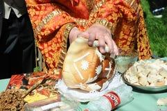 Las manos del corte del sacerdote adornaron el pan Foto de archivo libre de regalías