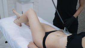 Las manos del cosmetólogo aplican el gel especial en caderas de la mujer antes del procedimiento de elevación, cámara lenta metrajes