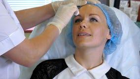 Las manos del cosmetólogo en los guantes de goma limpian la piel del cliente en salón de belleza Foto de archivo