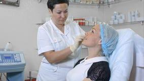 Las manos del cosmetólogo en los guantes de goma limpian la piel femenina del cliente en salón de belleza Imagenes de archivo