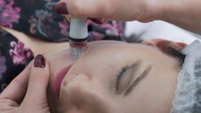 Las manos del cosmetólogo del primer hacen procedimiento de peladura hidráulico en cara de la mujer con el aparato médico, cámara almacen de video