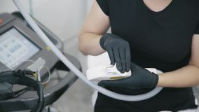 Las manos del cosmetologist del primer en guantes desinfectan el equipo antes de procedimiento del tratamiento almacen de video
