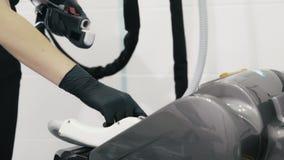 Las manos del cosmetologist del primer en guantes preparan el equipo del laser antes de procedimiento del tratamiento metrajes