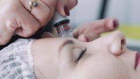 Las manos del cosmetologist del primer hacen procedimientos en cara paciente con el dispositivo de peladura hidráulico, cámara le almacen de video