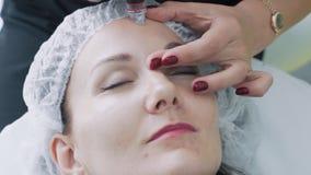 Las manos del cosmetologist del primer hacen procedimientos en cara paciente con el dispositivo de peladura hidr?ulico, c?mara le almacen de video