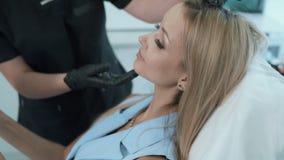 Las manos del cosmetologist del primer muestran en la zona de la cara del paciente para el procedimiento cosmético, steadicam tir almacen de metraje de vídeo