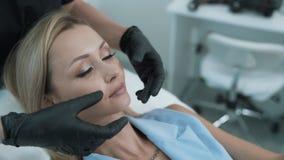 Las manos del cosmetologist del primer muestran en la zona de la cara del paciente para el procedimiento cosmético, steadicam tir almacen de video