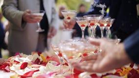 Las manos del ` de las huéspedes toman los vidrios con el vino que burbujea en el partido Los vidrios se construyen en las pirámi