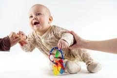 Las manos del ` de los padres ayudan al bebé a levantarse y a tomar la primera medida Fotos de archivo
