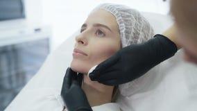 Las manos del doctor del primer de la c?mara lenta desinfectan y limpian la cara del paciente con el disco del algod?n antes del  almacen de metraje de vídeo