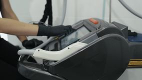 Las manos del doctor del primer en guantes giran el equipo del laser antes del procedimiento, c?mara lenta almacen de metraje de vídeo