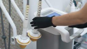 Las manos del doctor del primer giran el equipamiento médico antes del procedimiento, cámara lenta metrajes