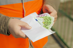 Las manos del empleado con los billetes de banco euro Imagen de archivo