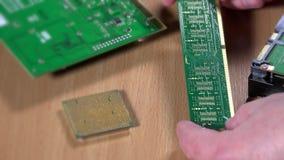 Las manos del especialista analizan componentes de ordenador Módulo de la memoria ram de  metrajes