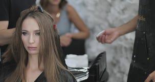 Las manos del estilista del peluquero están aplicando el tinte al pelo largo del ` s de la mujer metrajes