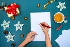 Las manos del famale con las decoraciones de la Navidad Fotografía de archivo libre de regalías
