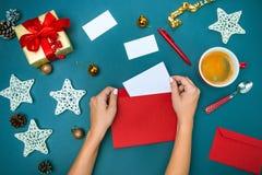 Las manos del famale con las decoraciones de la Navidad Imagen de archivo libre de regalías